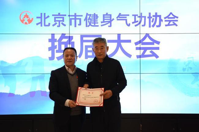 北京市体育总局秘书长王品熙同志为新任会长王玉明同志颁发就任聘书