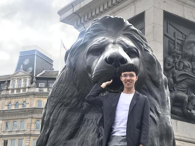 连笑手扶狮子雕像拍照留念