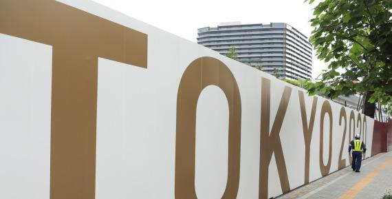 圖為一名工作人員從東京奧林匹克體育場的圍擋外走過。新華社記者 王子江 攝