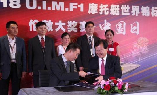 国际摩联F1委员、中国天荣集团董事局主席李浩杰(前右)与《欧洲时报》英国副总经理李强(前左)签署合作意向
