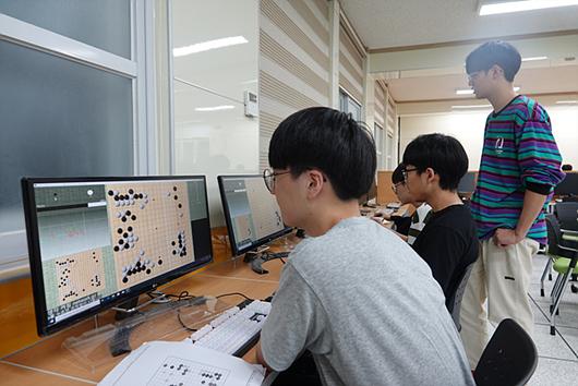 图为运动部学生在AI学习室研讨对局