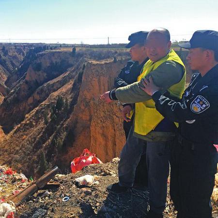 二〇一六年十二月十六日,在澄城县一个垃圾场,犯罪嫌疑人谢胜利在办案民警押解下指认作案工具丢弃点。