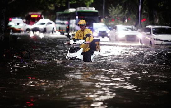 黄雁村十字附近,市民在积水里骑行。