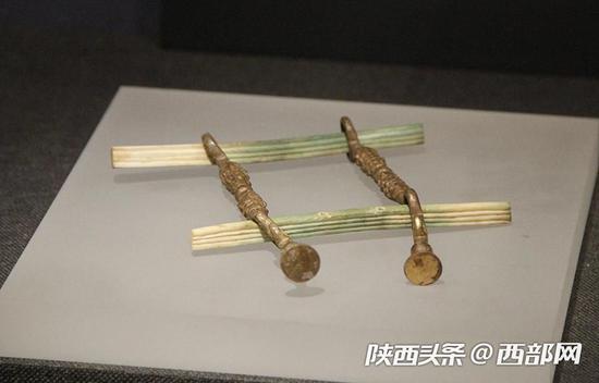 鎏金铜马衔,下方泛绿色骨镳为象牙制品。