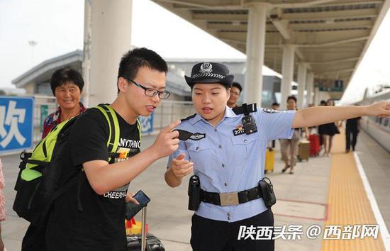 乘警郭婕敏在帮助旅客寻找自己的乘坐车厢