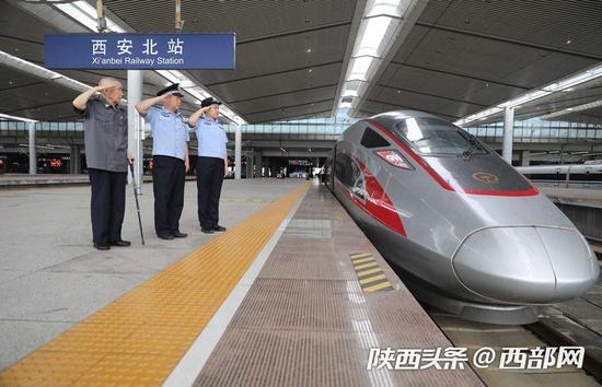 郭婕敏和父亲郭东、爷爷郭来仁一起来到西安北站,向一辆复兴号高铁列车敬礼