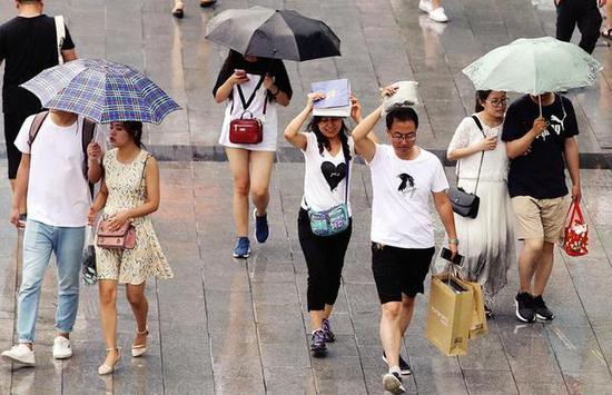 手提袋成了市民临时雨伞 本报记者马昭摄