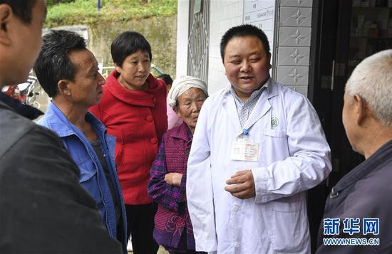 5月28日,何永清(右二)在村衛生室為群眾講解日常防病常識。