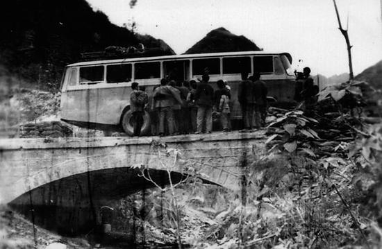 1976年,乘客在白河县茅坪镇龙王沟桥乘坐班车。 安康市交通运输局供图