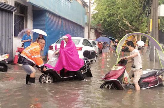 市政人员帮助市民安全过马路。本报记者代泽均摄