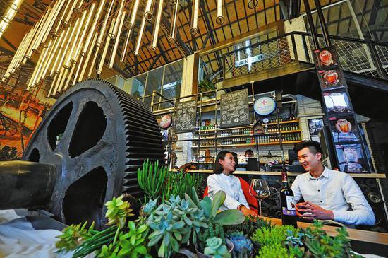 用废旧齿轮、螺丝等钢铁零件作为设计元素,改建后的陕西钢厂老厂房重获新生(2016年3月21日拍摄)。
