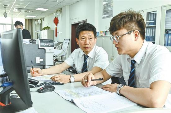 5月15日,孙西宁与年轻同事一起商议动车组调度检修工作。