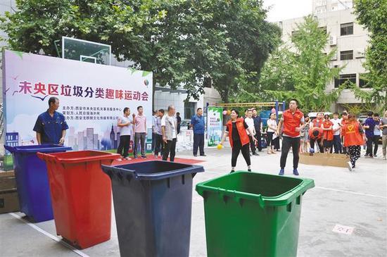 在垃圾投篮项目中,参赛选手把代表着不同类别垃圾的小球分别投放到相应的垃圾桶中。