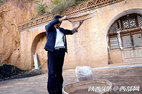 王不芳正在用传统方法筛选榨油的胡麻籽。