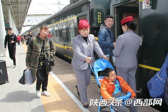 向金玉在汉中火车站帮助老人送孙子去广州探亲。