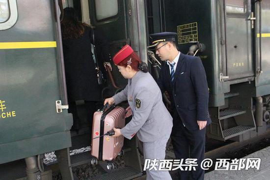 在安康火车站帮助旅客送行李上车。