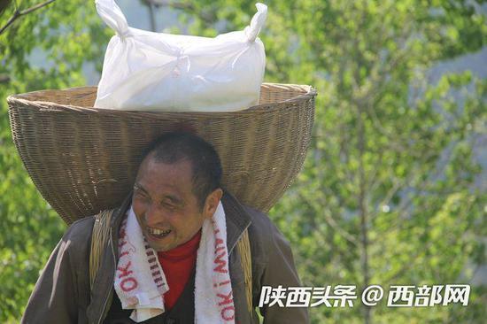 李安兴背着60斤挂面,行走在10里送货山路上。