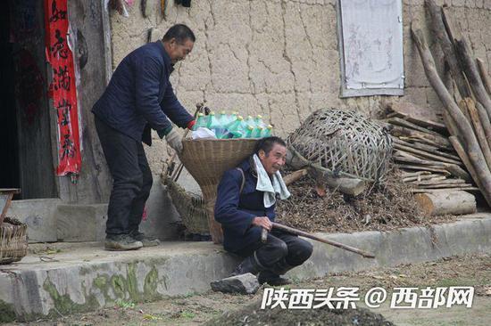 村民李华明帮助送货到家的李安兴卸货。