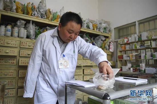 5月28日,何永清在村衛生室為就診群眾配制中草藥。