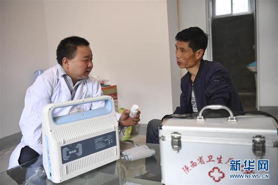 """5月28日,何永清(左)""""送医上门""""为村民文武看病。"""