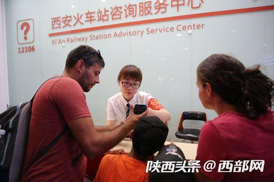 西安火车站工作人员在给旅客提供咨询服务 (摄影:金航)