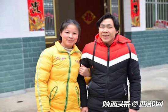 陈金兰与丈夫在新房前合影。