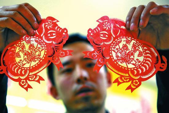 高河晓剪纸艺术培训中心的学员向记者展示剪纸作品。