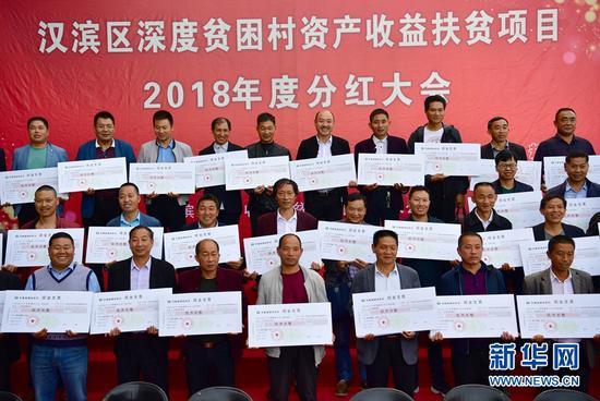 9月28日,在陕西省安康市汉滨区举行的深度贫困村资产收益分红大会上,来自当地深度贫困村的代表领取现金支票。记者邵瑞摄