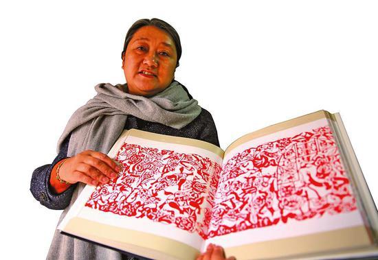 刘洁琼介绍自己和母亲高凤莲及外甥女樊蓉蓉三代人的剪纸作品。