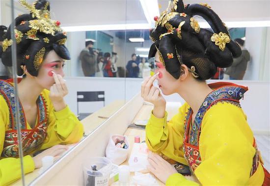 """11月23日,""""不倒翁女孩""""冯佳晨正在化装间化装,为晚上的演出做准备。本报记者 李旭佳摄"""