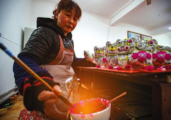 在六营村胡新明泥塑传承研习所里,工人用加热的颜料为泥塑进行彩绘。