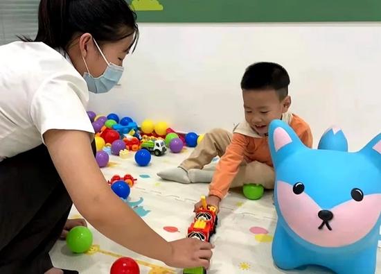 工作人员帮忙照看孩子