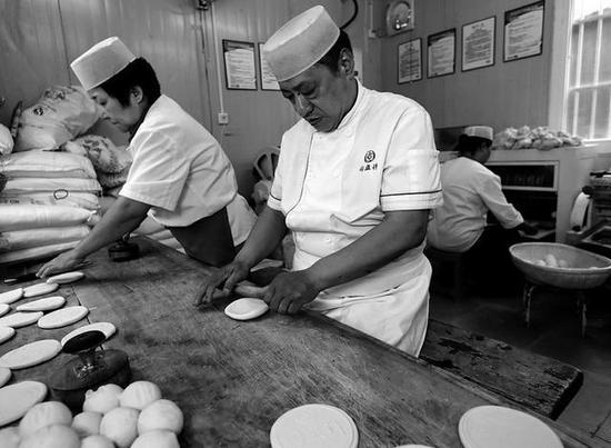 同盛祥非物质文化遗产传承人乌平正和同事一起制作牛羊肉泡馍专用饼