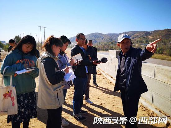 米脂县水务局副局长朱绪光正在向调研团介绍无定河治理情况。摄影 王耀丽