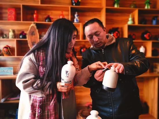 孟女士在哭泉村传统工艺玉米酒坊内咨询品质和价格。