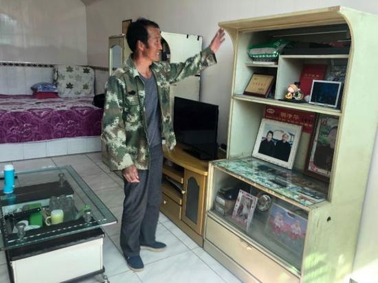 尹治军介绍当时结婚的老家具。记者曹槟摄
