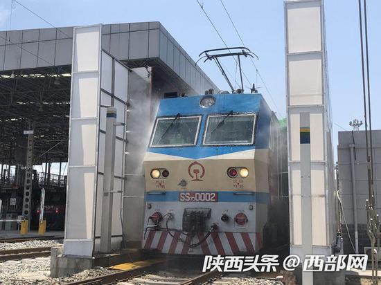 """西安机务段的机车头正在通过自动清洗设备完成""""火车头洗澡""""。"""