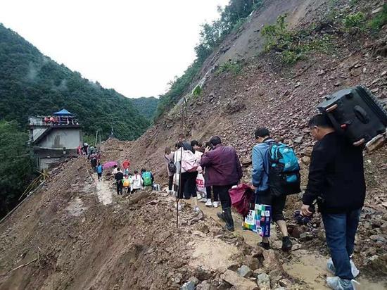 泥石流致G541国道南宫山段交通中断路人从便道通行 图片来源岚皋融媒体