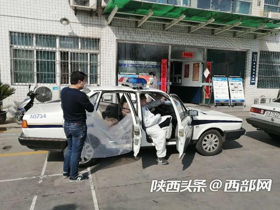 工作人员正在为警车安装隔离防护膜。