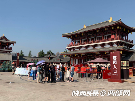 在大唐芙蓉园入口处,游客需戴好口罩、出示健康码和预约码、测量体温后才能入园。