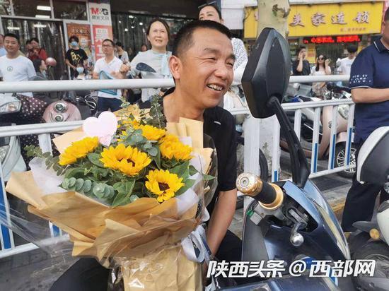 安康中学考点门前,不少爸爸也手捧鲜花,迎接顺利完成考试的孩子。