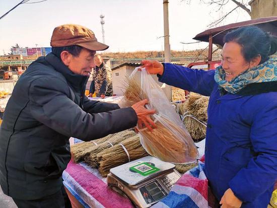 1月22日,王益区黄堡镇年集现场,市民正在选购红薯粉条。