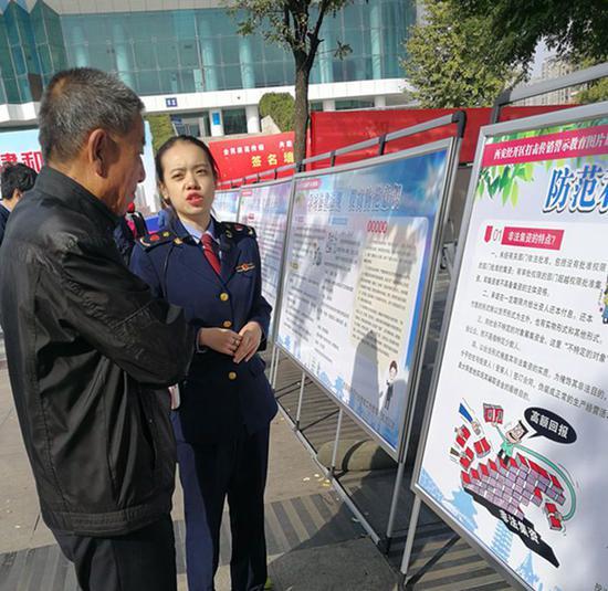 西安市工商局经开分局干部胡斯凡在活动现场为群众讲解法律知识。