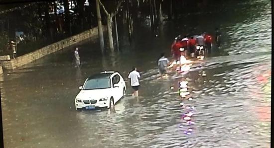 丰镐东路至桃园南路一路口,一车辆被困,行人司机纷纷前去帮忙