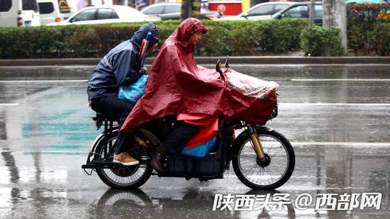 雨中骑摩托车出行的市民(资料图)