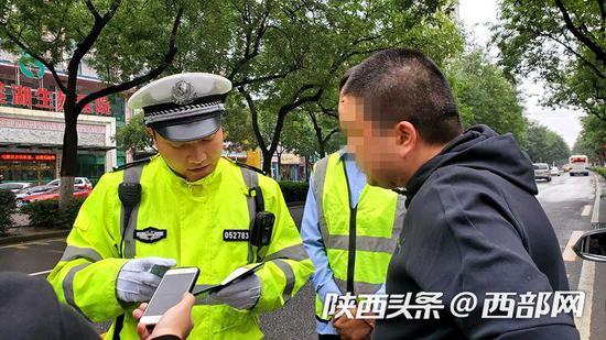 交警向驶上公交专用道的车辆驾驶员了解情况。