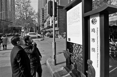 市民看标识牌    本报记者 王晓峰 摄