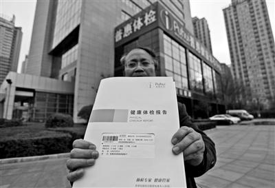 王女士的丈夫向记者出示体检报告 本报记者 王晓峰 摄