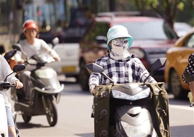7月8日,古城西安午后的街頭,出行的市民為防曬將自己裹得嚴嚴實實。記者 代澤均 攝
