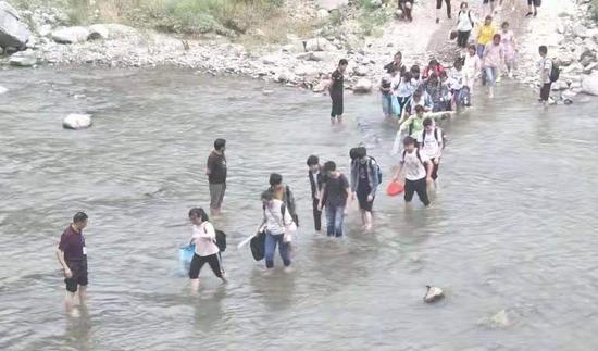 挽起裤脚 ,涉水过河。